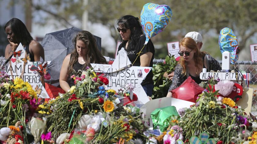 In this Feb. 25, 2018 file photo, mourners bring flowers as they pay tribute at a memorial for the victims of the shooting at Marjory Stoneman Douglas High School, in Parkland, Fla.