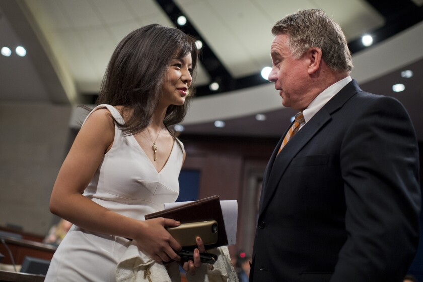 Anastasia Lin, Miss World Canada 2015, talks with Rep. Chris Smith (R -N.J.) before a hearing on China in July.