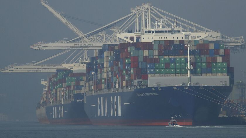 Container ships waiting to be unloaded are seen through a thick haze at the Port of Oakland as smoke from the massive Camp fire drifts south, polluting the air.
