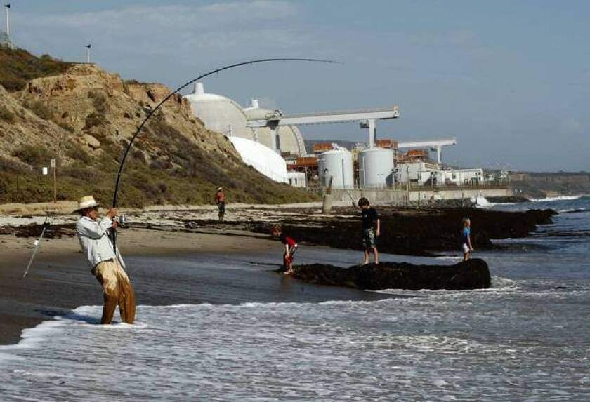 People play at the beach near the San Onofre Nuclear Generating Station in northern San Diego County. The plant has been shut down since January in the wake of equipment problems that caused a release of radioactive steam into the atmosphere.