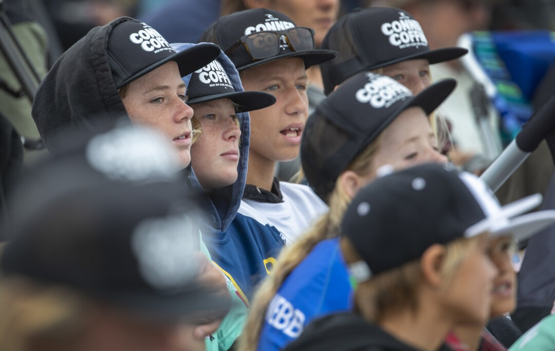 All wearing Conner Coffin hats, young fans watch their favorite surfer, Conner Coffin compete against Morgan Cibilic