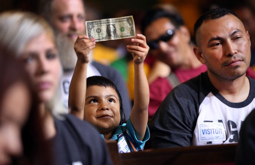 David Lazo, 5, holds a dollar bill as his father, Francisco, watches the City Council debate on raising the minimum wage on June 3. The panel voted to raise the minimum wage to $15 an hour by 2020.