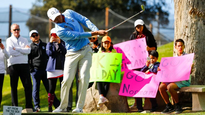Norman Xiong tees off on the first hole at Colina Park Golf Course as fans hold signs for him and Tiffany Joh.