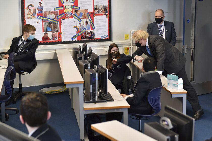 El primer ministro británico, Boris Johnson, a la derecha, choca el codo de una alumna de 7mo año
