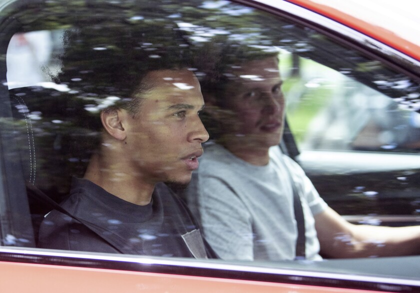 FC Bayern soccer club newcomer Leroy Sane, left, sits in a car as he leaves the FC Bayern training ground in Munich, Germany, July 2, 2020. FC Bayern newcomer Sane arrived in Munich the day before. (Matthias Balk/dpa via AP)