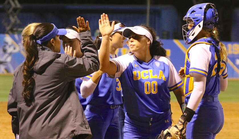 Pitcher Rachel Garcia high-fives UCLA coach Kelly Inouye-Perez after the final out of the 2018 Los Angeles regional final. The Bruins beat Cal State Fullerton 6-4.