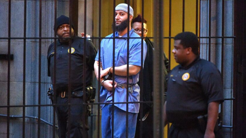 """Officials escort """"Serial"""" podcast subject Adnan Syed from the courthouse on Feb. 3, 2016, following the first day of hearings for a retrial in Baltimore."""