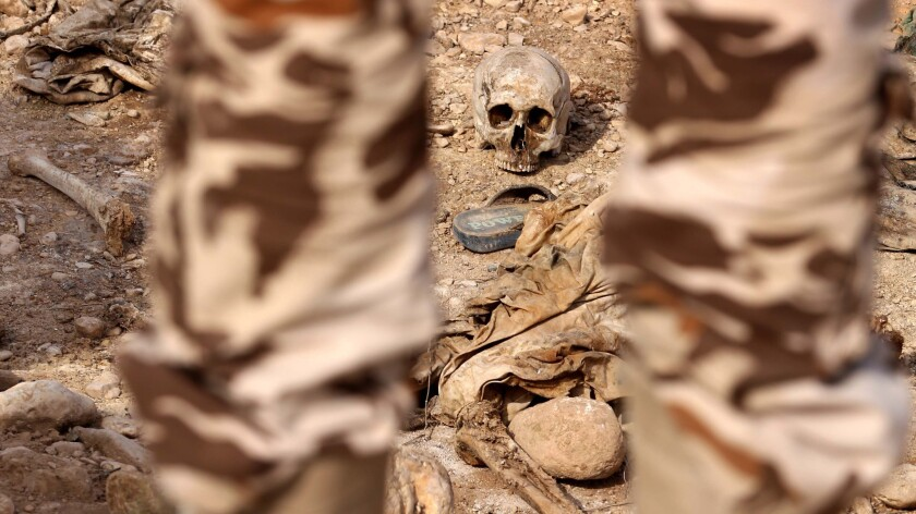 This file photo from 2015 shows a member of the Kurdish forces looking at the remains of Yazidis reportedly killed by Islamic State militants.