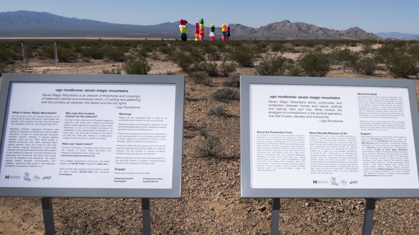 "Signage explains the purpose of the art installation called ""Seven Magic Mountains."" Located south of Sin City, it's the work of Swiss artist Ugo Rondinone."