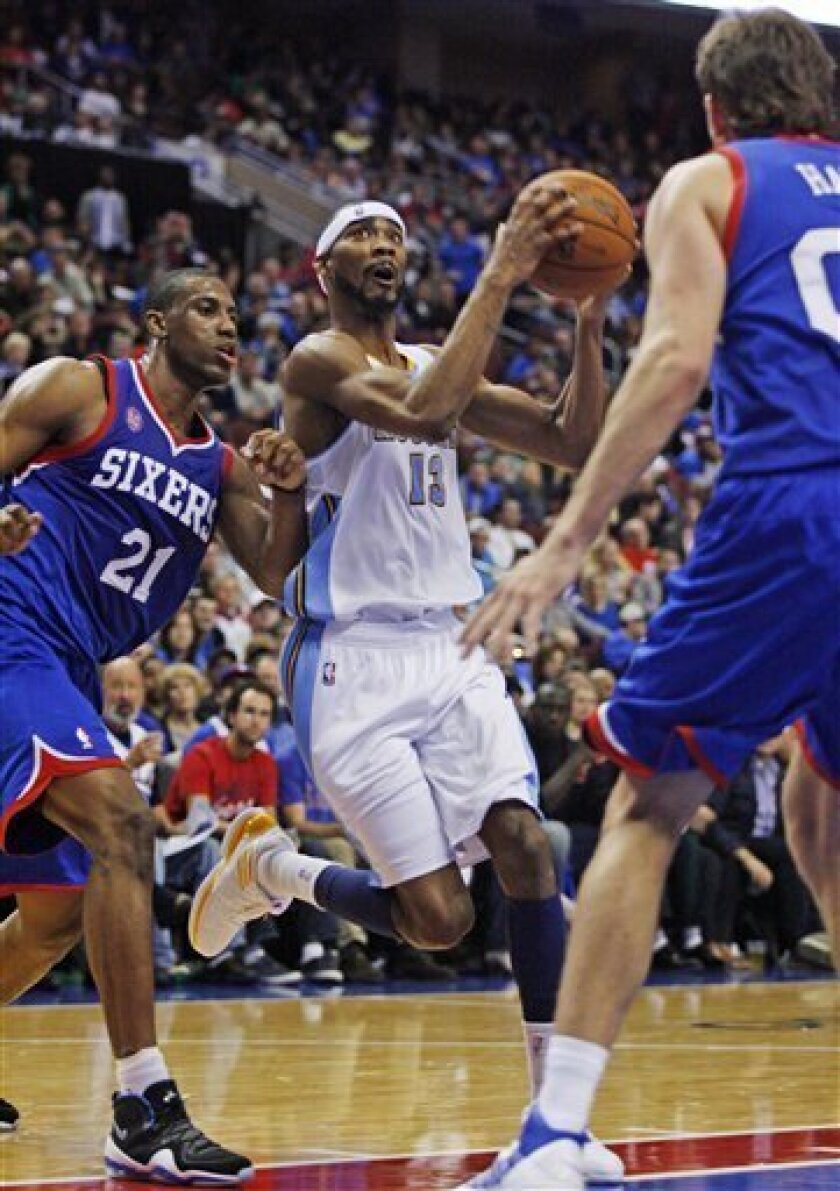 Denver Nuggets' Corey Brewer (13) looks to shoot against Philadelphia 76ers' Thaddeus Young (21) and Spencer Hawes (00) in the first half of an NBA basketball game, Wednesday, Oct. 31, 2012, in Philadelphia. (AP Photo H. Rumph Jr)