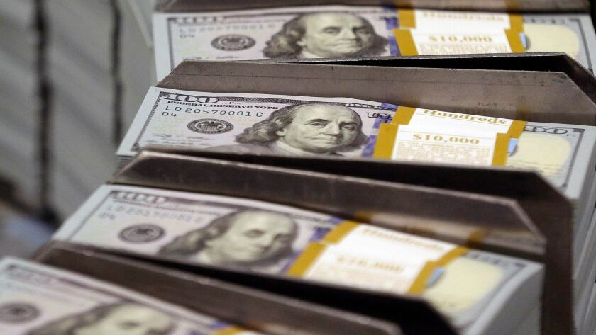 FILE - In this Sept. 24, 2013, file photo, freshly cut stacks of $100 bills make their way down the