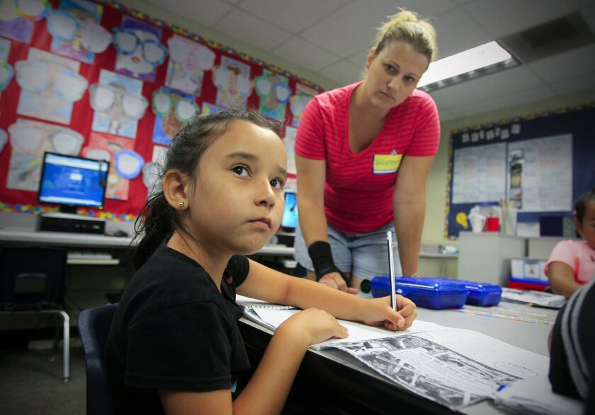 Celeste Ramirez, a third grader at Myrtle S. Finney Elementary School listens and writes during a reading lesson as volunteer Chenoa Cavanaugh looks on.