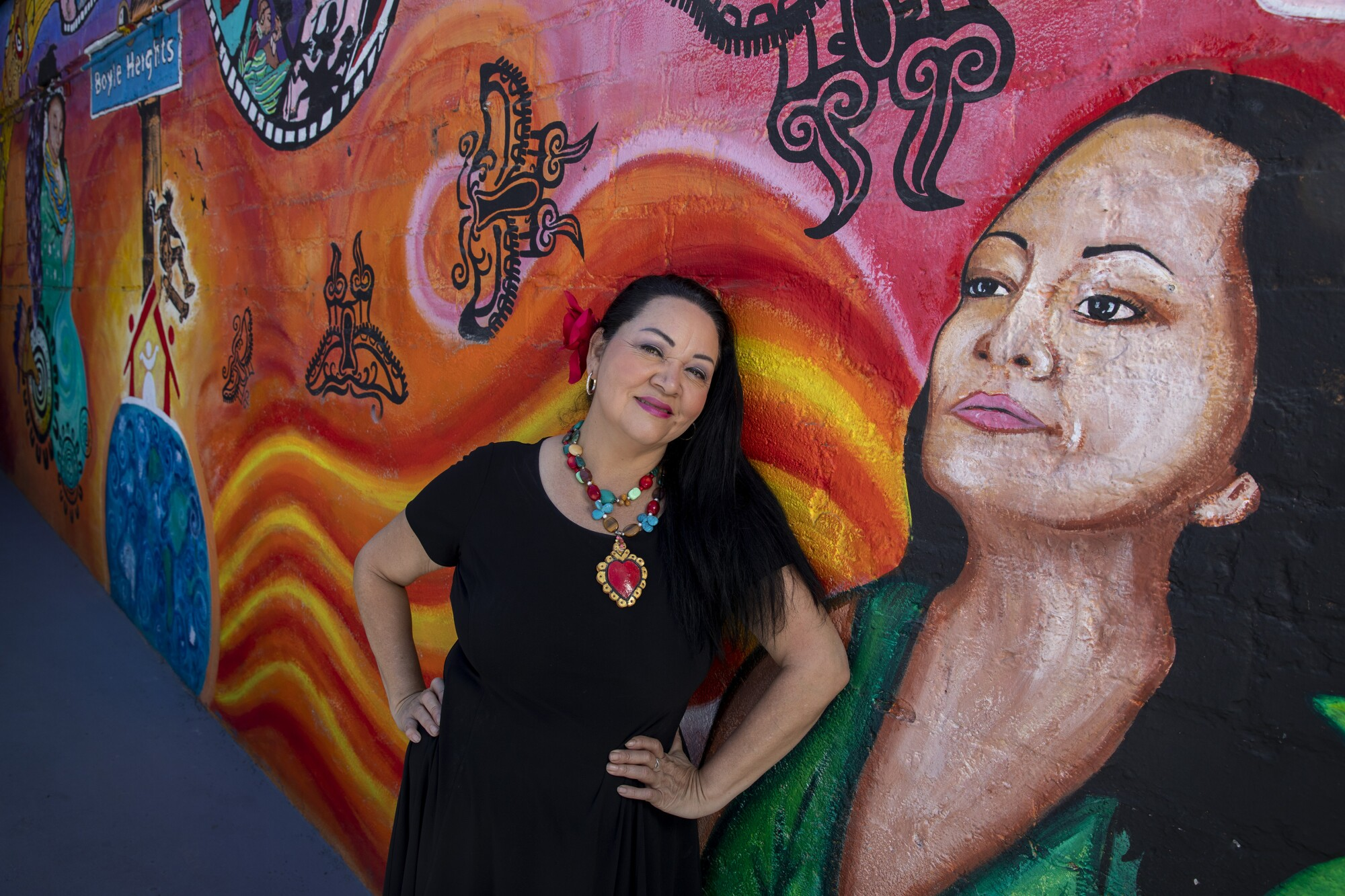 Founding artistic director Josefina Lopez sits outside Casa 0101 with a mural of herself July 31, 2021 in Boyle Heights