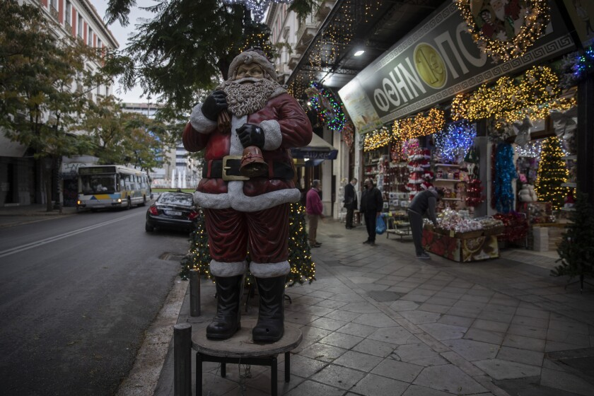 A Santa Claus stands outside a Christmas decoration shop, in central Athens, on Monday, Dec. 7, 2020. Despite a significant drop in cases over the past week, authorities have extended the countrywide lockdown to Dec. 14, but have allowed certain shops, including those selling Christmas-related merchandise, to open from Monday. (AP Photo/Petros Giannakouris)