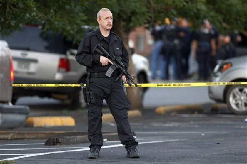 A SWAT team officer stands watch near an apartment house where the suspect in a shooting at a movie theatre lived in Aurora, Colo., Friday, July 20, 2012. As many as 14 people were killed and 50 injured at a shooting at the Century 16 movie theatre early Friday during the showing of the latest Batm
