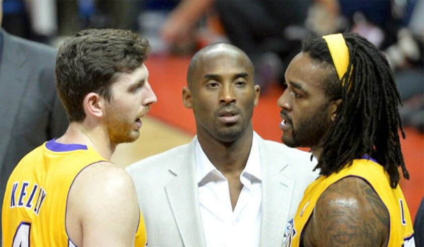 Lakers rookie Ryan Kelly, left, and Jordan Hill, right, are joined by Kobe Bryant during an exhibition game in October.