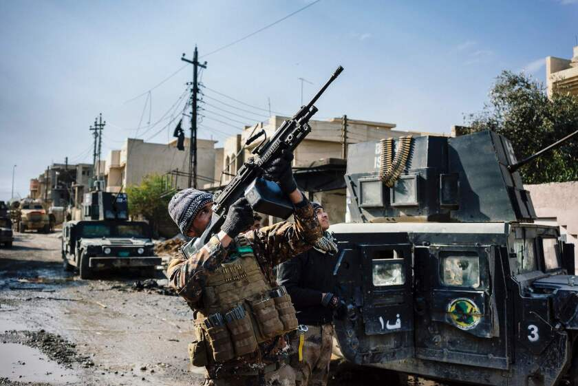 An Iraqi Counter Terrorism Service member shoots at a drone flown by Islamic State militants in Mosul's Rifaq neighborhood on Jan. 8, 2017.