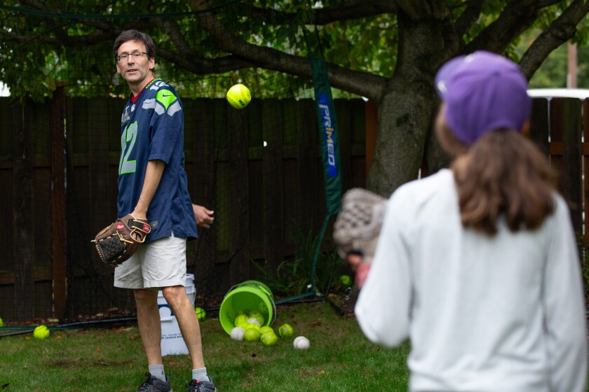Bob Ferguson and his daughter Katie, 11, practice behind-the-back pitching at their Seattle home.