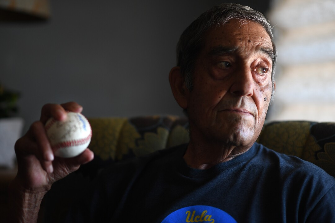 Art Velarde holds an autographed baseball from his living teammates at his home in Hacienda Heights.
