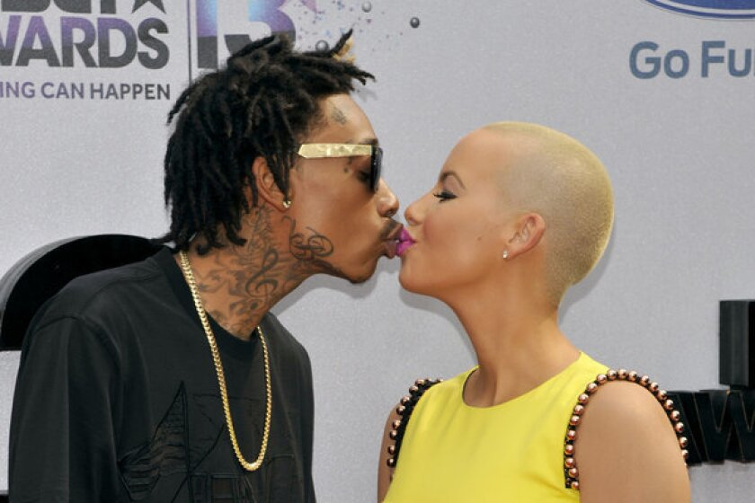 Wiz Khalifa, left, and Amber Rose — smooching at the BET Awards in June — got married Monday.