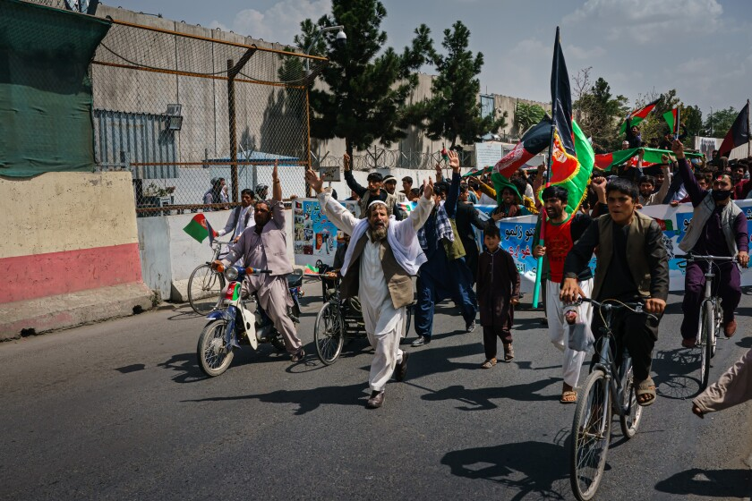 People on foot and on bicycles march down a street carrying red, black and green flags