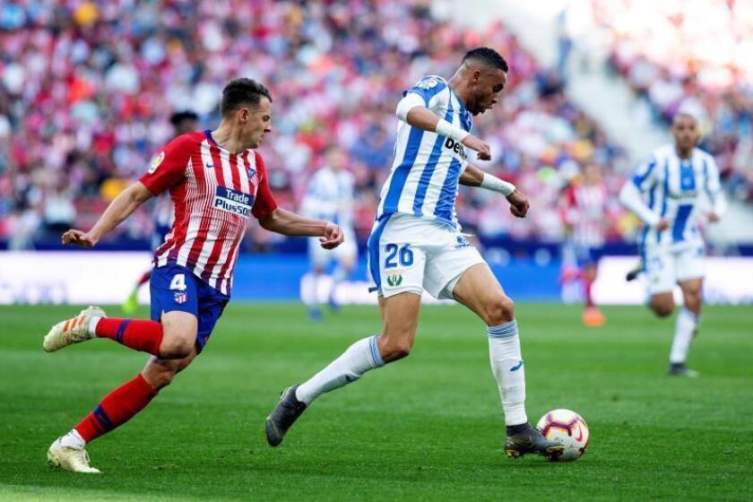 El defensa colombiano del Atlético de Madrid, Santiago Arias (i), lucha por el balón ante el delantero marroquí del Leganés, Youssef En-Nesyri (d), durante el partido de La Liga disputado en el estadio Wanda Metropolitano en Madrid. EFE