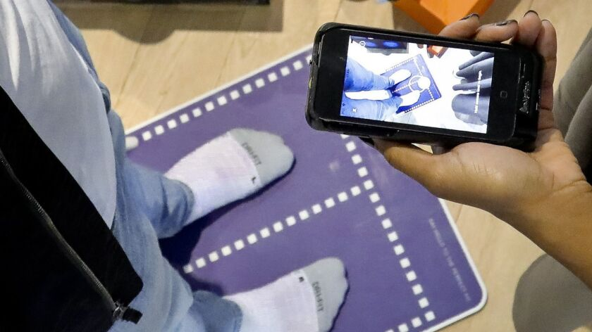 Nike officials demonstrate the company's foot-scanning tool on its app that will measure and remembe