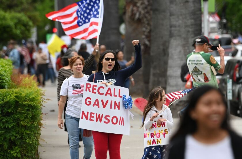 A woman raises her fist while shouting with a sign that says Recall Gavin Newsom
