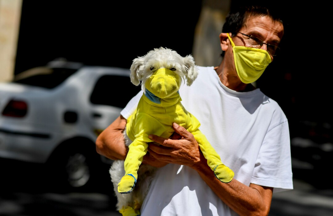 VENEZUELA: A man wears a face mask March 20 while he carries his dog with a protective suit as a preventive measure against the coronavirus spread in Caracas, Venezuela.