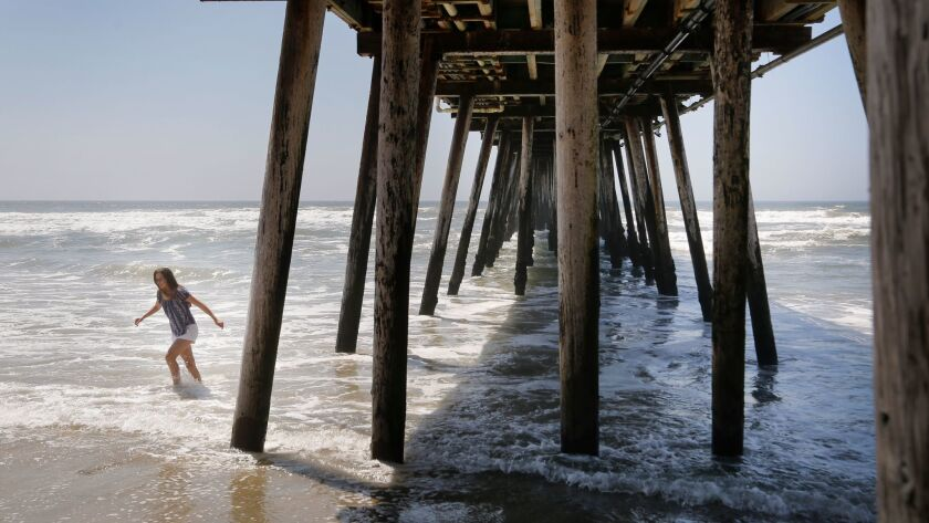 A young woman wades into water under the Imperial Beach Pier in April 2017. City officials joined six other California coastal communities in a lawsuit against oil companies, claiming the corporations should pay for the effects of climate change.