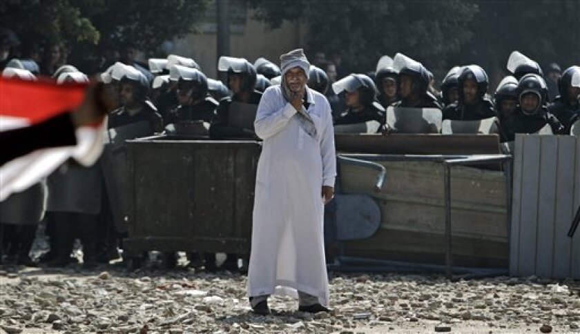 An Egyptian man stands in front of riot police blocking the road during clashes with protestors near the Interior Ministry in Cairo, Egypt, Saturday, Feb. 4, 2012. The number of people killed in clashes with Egyptian security forces in the wake of a deadly soccer riot rose to 11 on Saturday, according to a field doctor and a security official, as demonstrators in Cairo kept up their calls for an end to military rule and retribution for those killed in the soccer game violence. (AP Photo/Muhammed Muheisen)