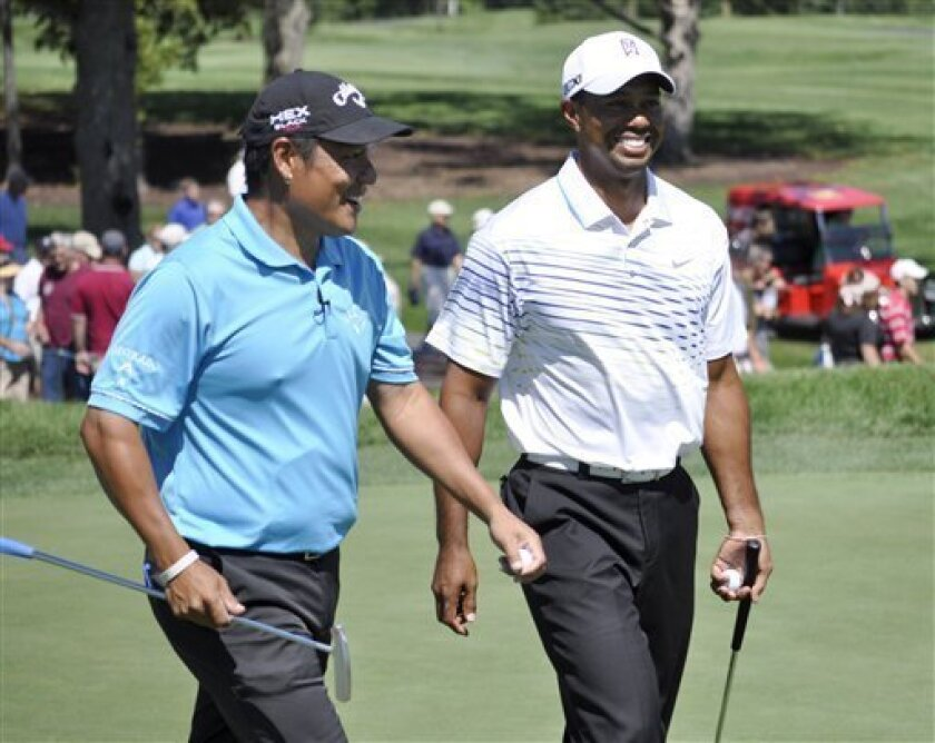 Notah Begay III, left, and Tiger Woods share a laugh as they walk off the eighth green during the fifth annual Notah Begay III Foundation Challenge at Atunyote Golf Club at Turning Stone Resort and Casino in Verona, N.Y., Wednesday, Aug. 29, 2012. (AP Photo/ KevinRivoli)