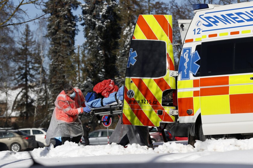 Medical workers move a covid-19 patient at a hospital overrun by the covid pandemic in Cheb, Czech Republic, Friday, Feb. 12, 2021. The Czech government has imposed a complete lockdown of the three hardest-hit counties to help contain the spread of a highly contagious variant of the coronavirus. The meeasures will became effective Friday for the two counties in western Czech Republic on the German border Cheb and Sokolov and another county in the northern part of the country Trutnov located on the border with Poland. (AP Photo/Petr David Josek)