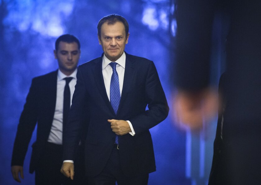 European Council President Donald Tusk, center, approaches Romanian President Klaus Iohannis, right, after arriving at the Cotroceni presidential palace in Bucharest, Romania, Monday, Feb. 15, 2016. Tusk visited Romania on Monday and warned of a possible European Union break-up after discussing the