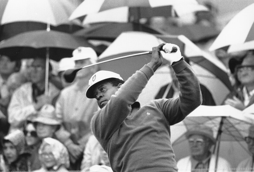 Lee Elder finishes a golf swing.