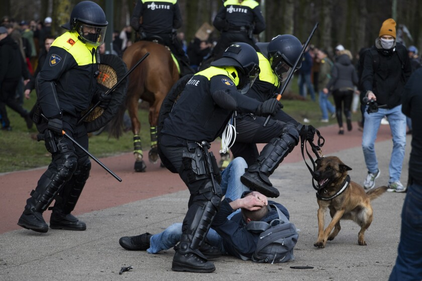 Dutch riot police kick a man during a demonstration to protest government policies including the curfew, lockdown and coronavirus related restrictions in The Hague, Netherlands, Sunday, March 14, 2021. Thousands of people took part in the rally ahead of three days of voting starting Monday in a general election. (AP Photo/Peter Dejong)