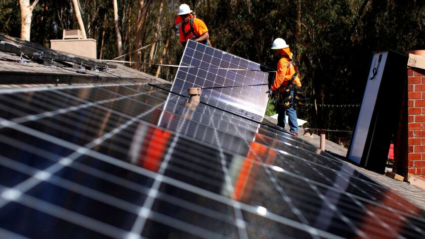 FILE PHOTO: Solar installers from Baker Electric place solar panels on the roof of a residential home in Scripps Ranch, San Diego, California