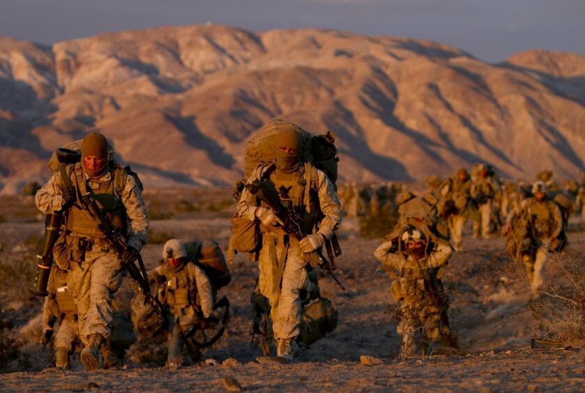 Marines carry their gear at sunrise as they prepare for another day of training during the new month-long ITX at Twentynine Palms.