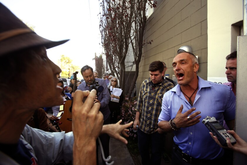 Mark Lipman, with People Organized for Westside Renewel, left, argues with Sebastian de Kleer, owner of Globe Homes and Condos, at a protest in Venice on Wednesday. The firm had many of its L.A. Airbnb listings removed this week.