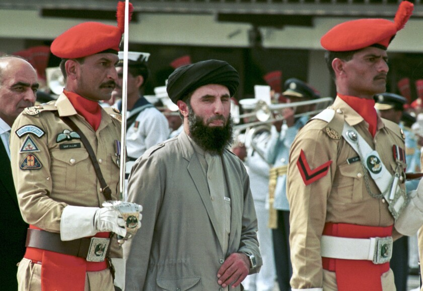 Gulbuddin Hekmatyar, center, passes in front of an honor guard in Kabul, Afghanistan's capital, in June 1996.