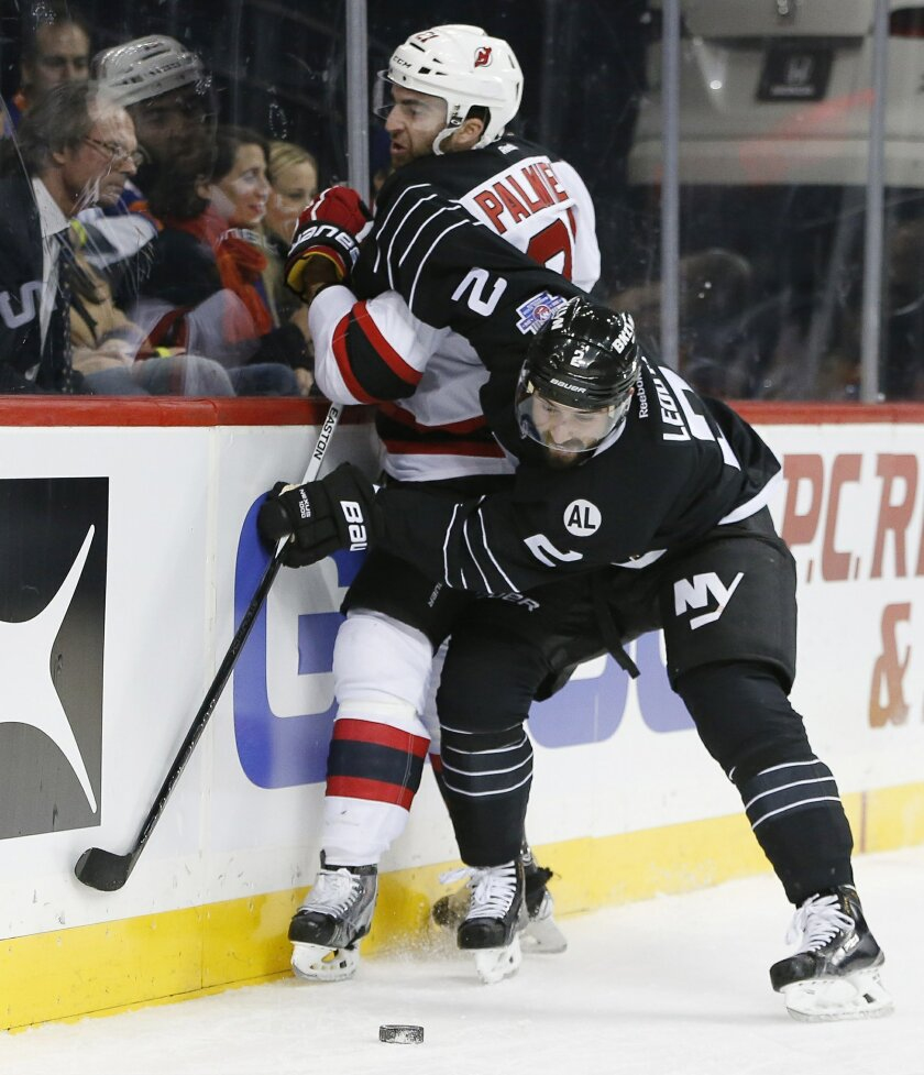 New York Islanders defenseman Nick Leddy (2) pins New Jersey Devils right wing Kyle Palmieri (21) against the boards during the first period of an NHL hockey game in New York, Tuesday, Nov. 3, 2015. (AP Photo/Kathy Willens)
