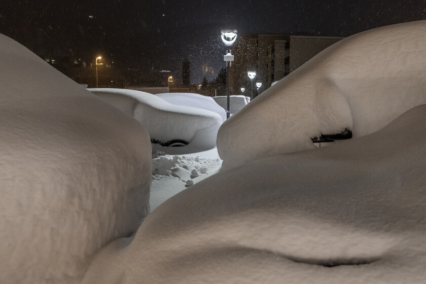 Cars are covered with snow in St. Moritz, Switzerland, Saturday, Dec. 5, 2020. Due to a heavy snowfall and strong wind, the FIS decided to cancel women's Super-G race of the FIS Alpine Ski World Cup on Saturday. (Jean-Christophe Bott/Keystone via AP)