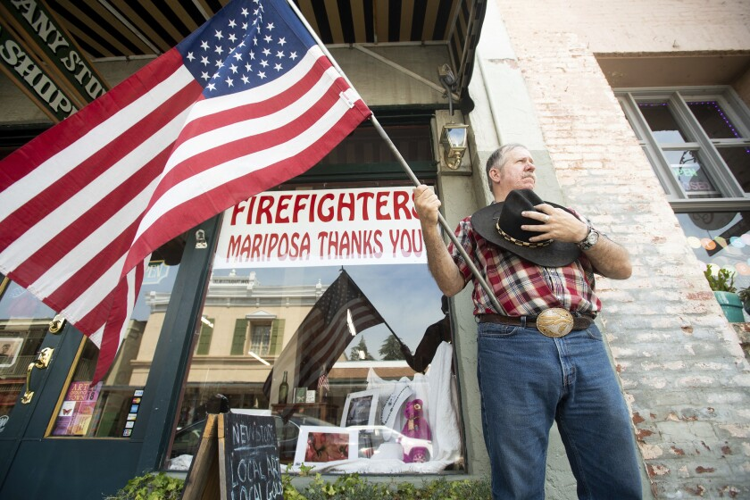Charles Phillips waits for a procession carrying the body of firefighter Braden Varney in Mariposa, Calif. Varney died Saturday while battling the Ferguson fire when his bulldozer overturned.