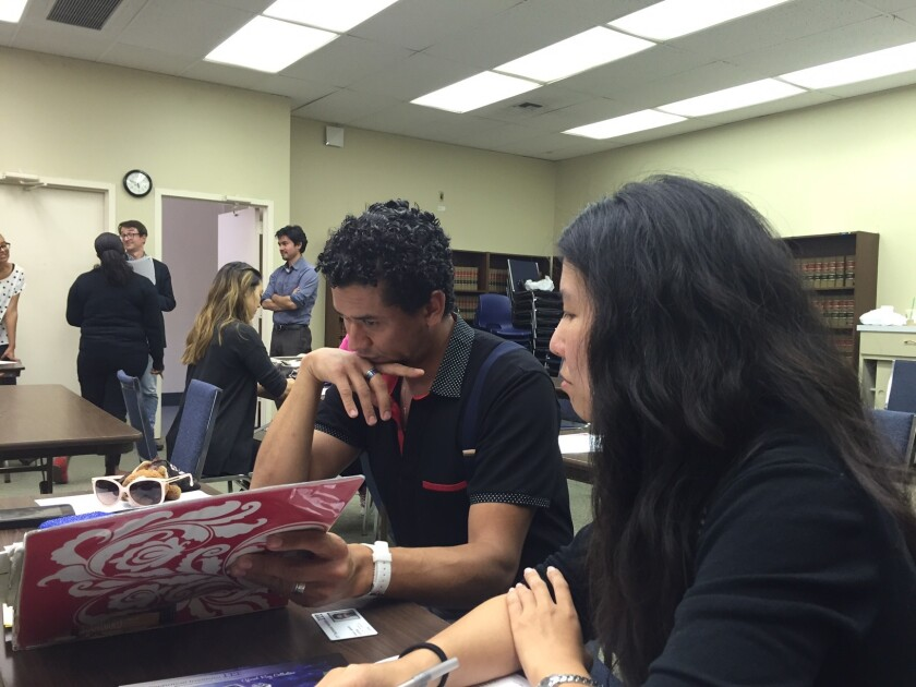 Alvaro Laborin, left, discusses his options with attorney Stephanie Lin of the Legal Aid Foundation of Los Angeles on Thursday after the closure of ITT Technical Institute's Torrance campus, where he had been studying cybersecurity.