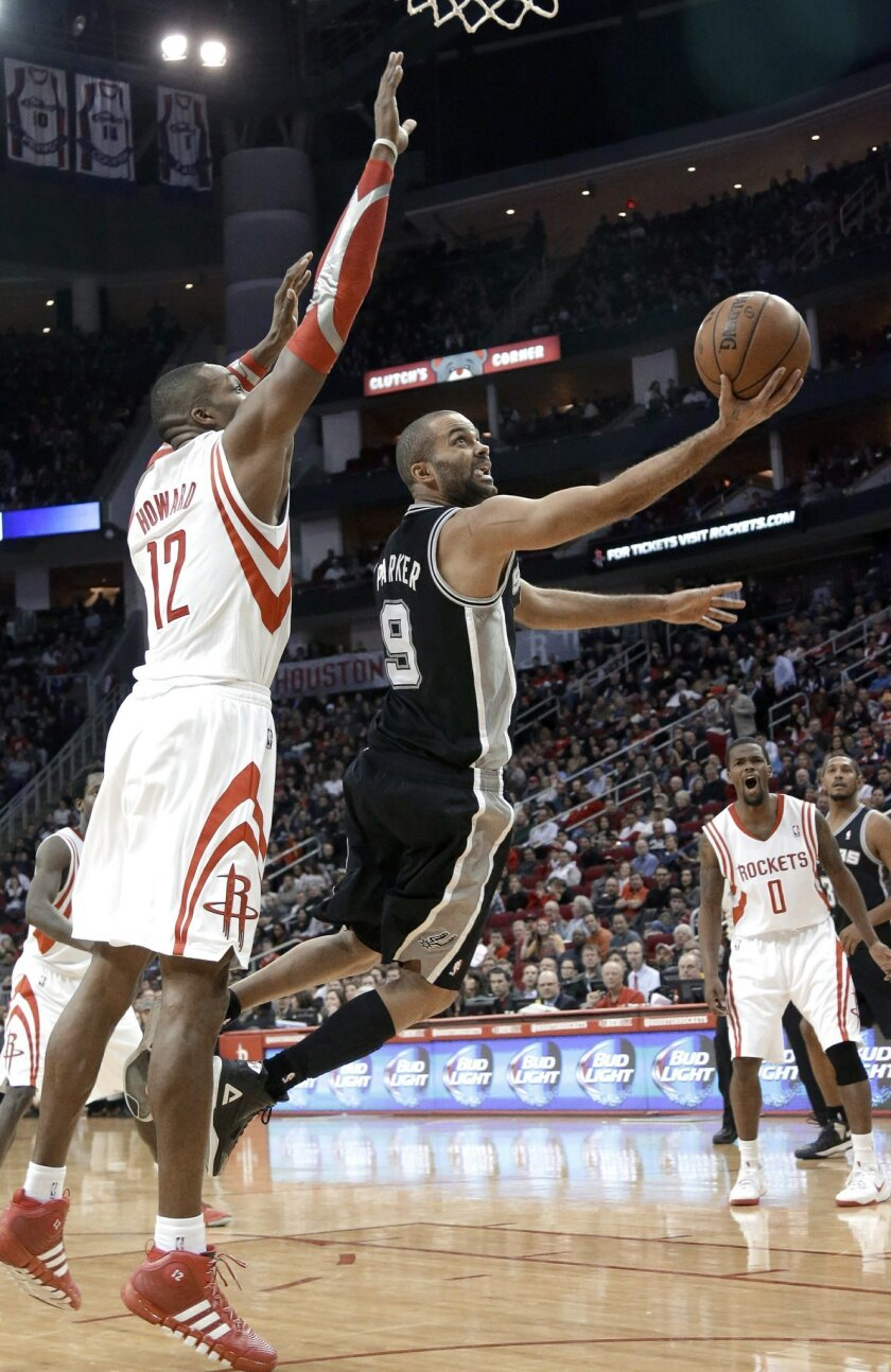 San Antonio Spurs' Tony Parker (9) goes to the basket against Houston Rockets' Dwight Howard (12) as Aaron Brooks (0) watches during the second half of an NBA basketball game Tuesday, Jan. 28, 2014, in Houston. The Rockets won 97-90. (AP Photo/Pat Sullivan)
