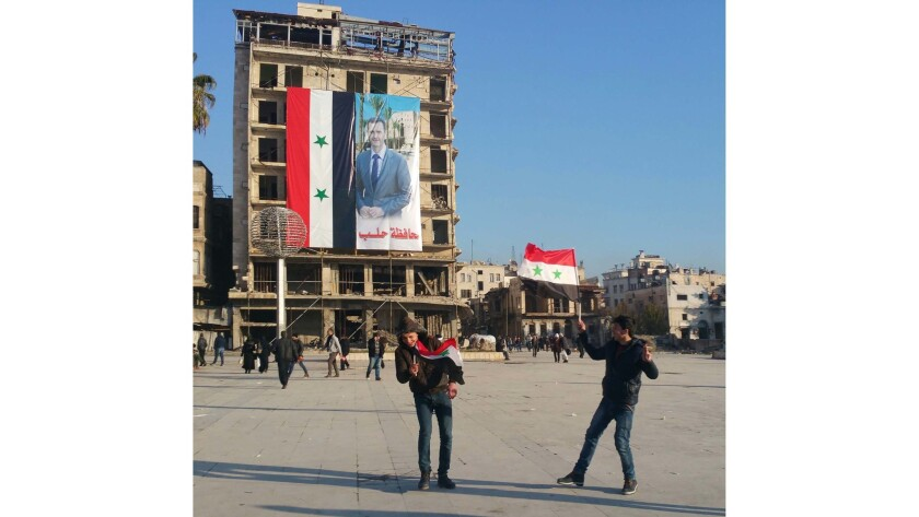 Boys pretend to joust in front of a Syrian government flag in Aleppo.