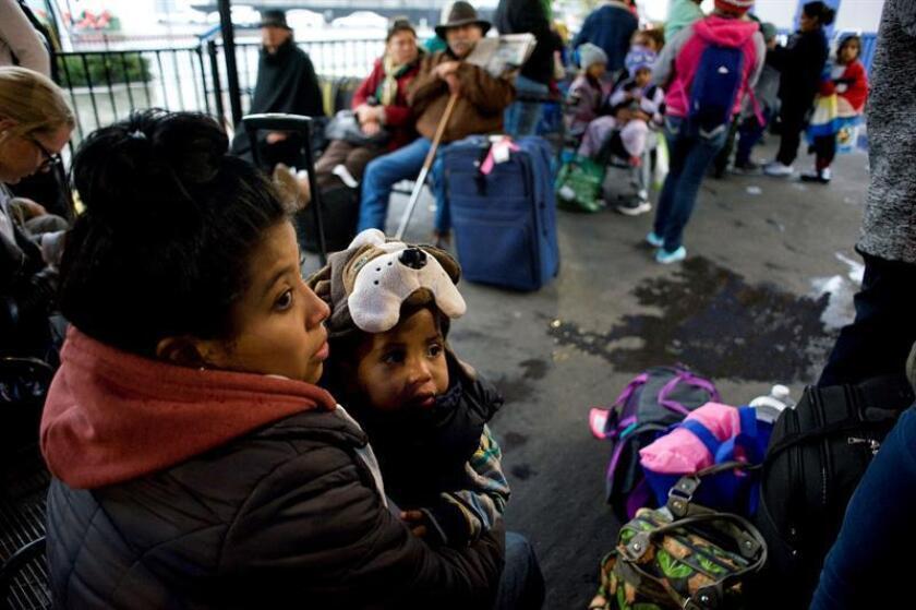 Maryuri (i), de 19 años, junto a sus hijo Santiago (c), de dos años, espera hoy en una parada de autobús para viajar con dirección a Ohio, en San Diego, California (EE.UU.). EFE/Arcguvi