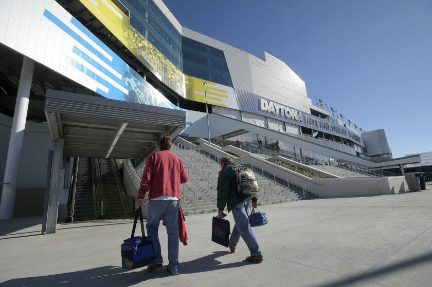 """In this Feb. 13, 2016,  photo, guests walk to one of the escalators comprising the fan injector system at Daytona International Speedway in Daytona Beach, Fla. The project was such a massive undertaking that architects had to account for the curvature of the Earth. It also got its own nickname, """"Da"""