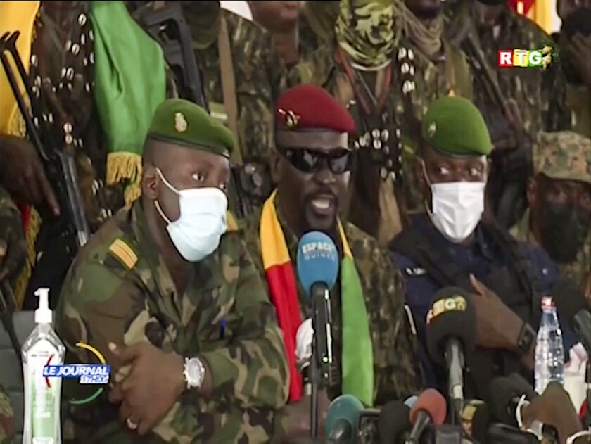 In this image made from video, Junta leader Col. Mamady Doumbouya, center, wearing a red beret and sunglasses, addresses officials in the capital Conakry, Guinea Monday, Sept. 6, 2021. Guinea's new military leaders sought to tighten their grip on power Monday after overthrowing President Alpha Conde, ordering the soldiers from his presidential guard to now join the junta forces and barring government officials from leaving the country. (Radio Television Guineenne via AP)