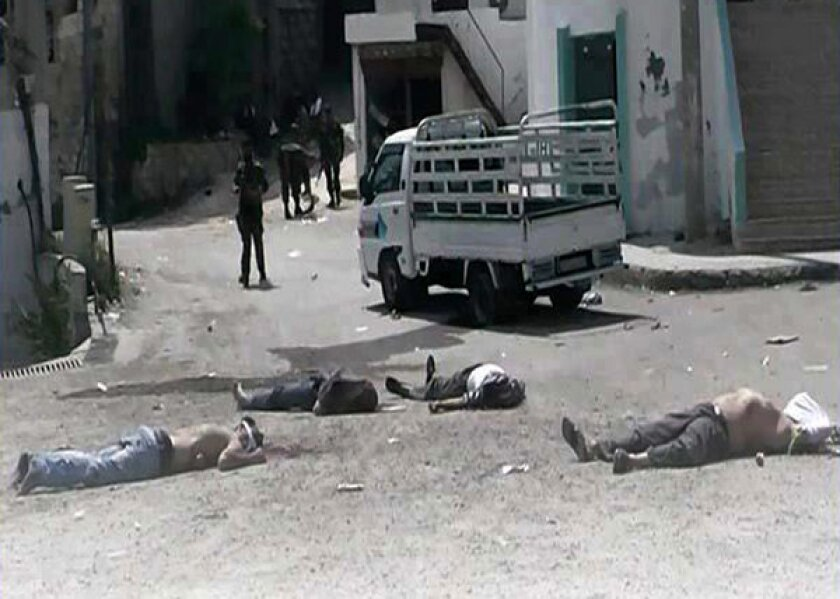 Opposition activists provided this image purporting to show Syrian soldiers standing near bodies in Bayda village.